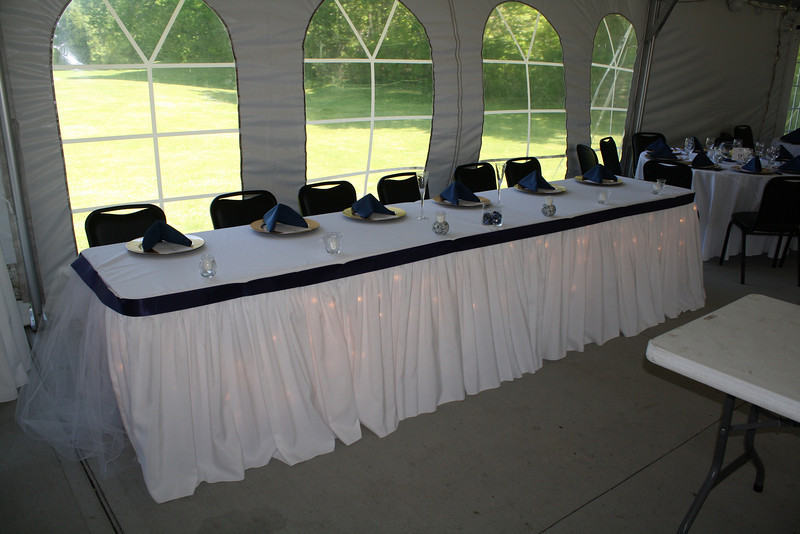 Tent wedding The head table is decorated simply with underlighting and navy
