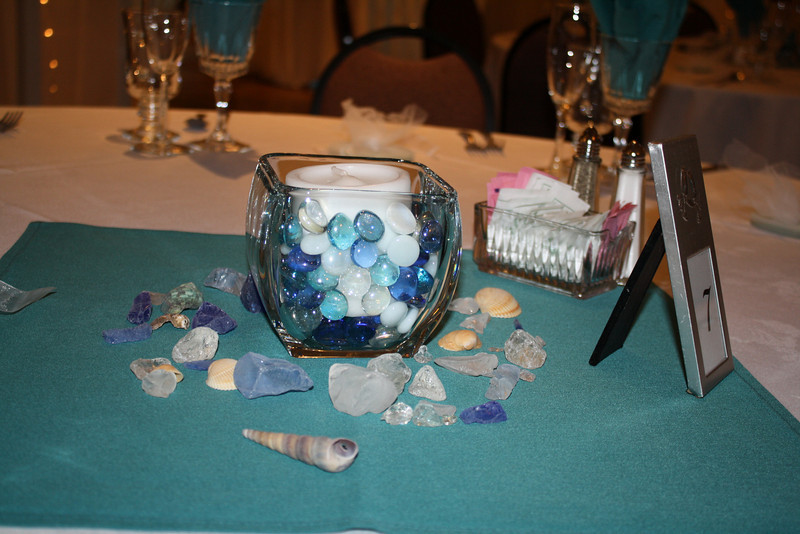 Centerpiece The bride chose small centerpieces surrounded by beach glass